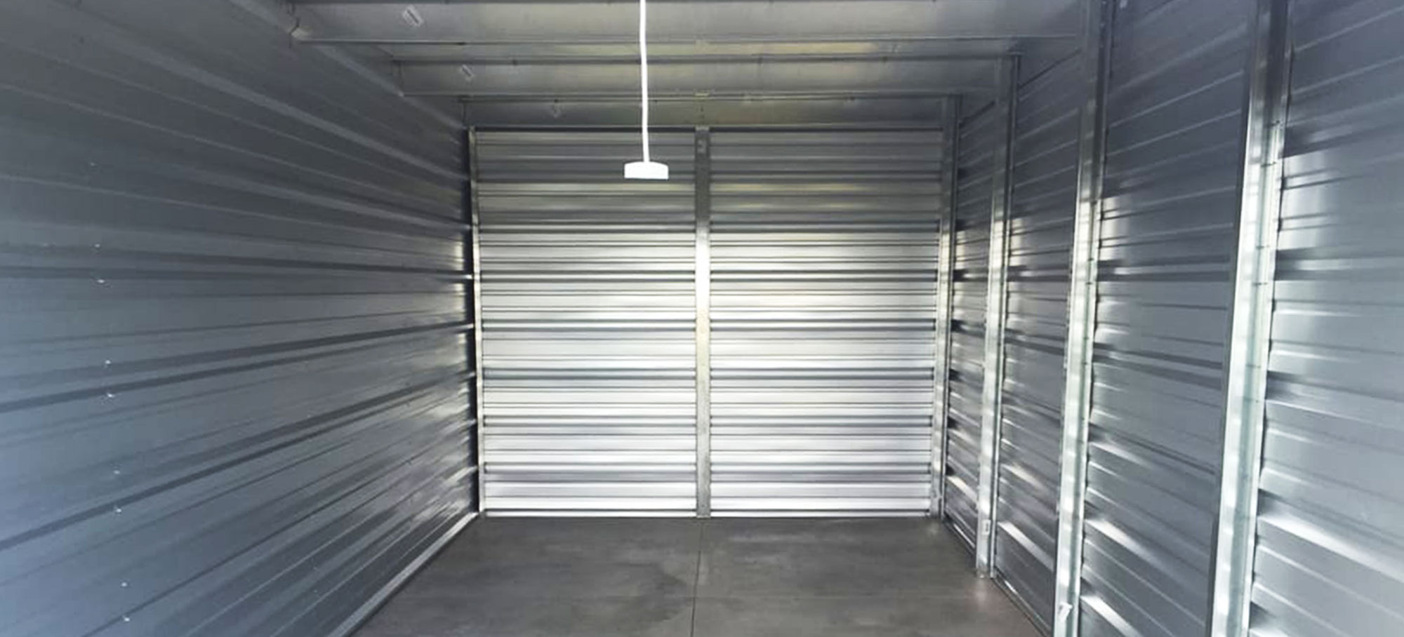 Interior of a self-storage unit at Randolph Storage featuring clean steel side walls, a well-maintained concrete floor, and easy-access overhead door