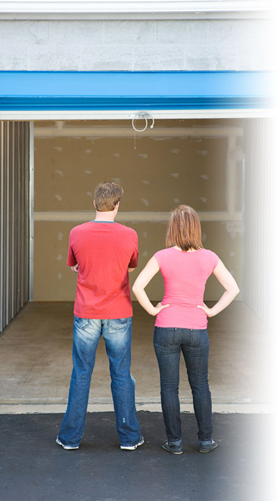 Young couple standing infront of an empty storage unit